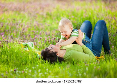 Happy woman and child in the blooming spring garden. Mum and son playing, hugging and smiling. Family holiday and togetherness.