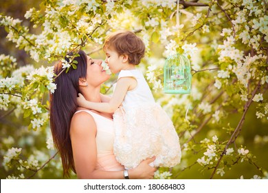 Happy woman and child in the blooming spring garden.Child kissing woman. Mothers day holiday concept