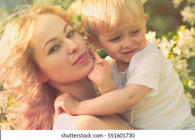 Happy woman and child in the blooming spring garden. Mothers day holiday concept