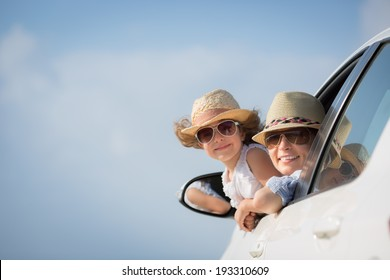 Happy woman and child in car against blue sky background. Summer vacation concept