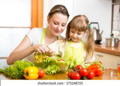 Happy woman and child cooking at kitchen
