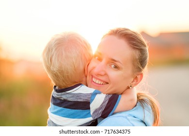 Happy woman and child having fun outdoors.  Family lifestyle rural scene of mother and son in sunset sunlight.