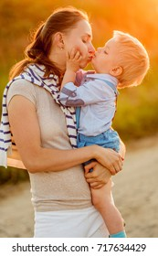 Happy woman and child having fun outdoors.  Family lifestyle rural scene of mother and son in sunset sunlight. Mother kissing her son.