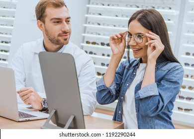 happy woman choosing eyeglasses and looking at mirror while male oculist standing near with laptop in optics