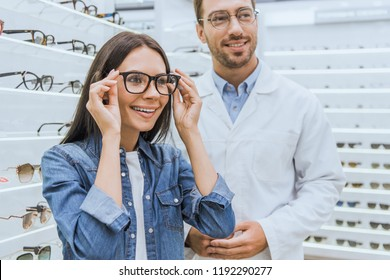 happy woman choosing eyeglasses while male oculist standing near in ophthalmic shop
