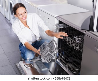 Happy woman choosing new dish washing machine in supermarket
