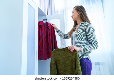 Happy woman choosing outfit from wardrobe closet with stylish clothes and home stuff