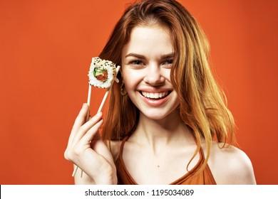 happy woman with chopsticks sushi rolls