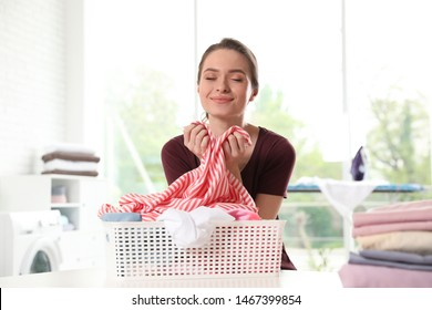 Happy woman with clean laundry at table indoors
