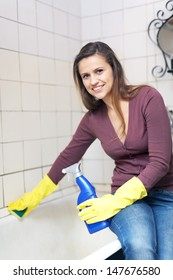 Happy woman cleaning  bathtub in bathroom at home