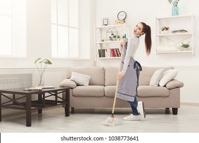 Happy woman cleaning home, dancing with mop and having fun, copy space. Housework, chores concept
