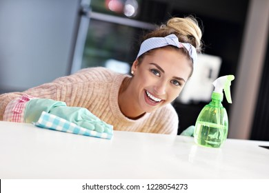 Happy woman cleaning kitchen countertop