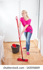 Happy woman cleaning and mopping floor at home.