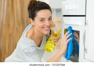 happy woman cleaning oven at home kitchen