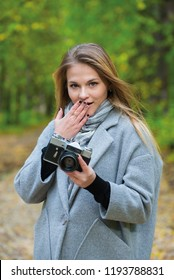 Happy woman in coat holding retro camera in hands portrait of teenage girl with long blond hair and retro camera in hands on bright blurred autumn background.