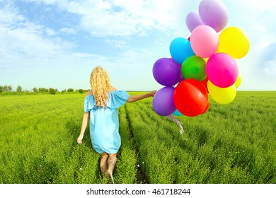 Happy woman with colorful balloons in field on blue sky background
