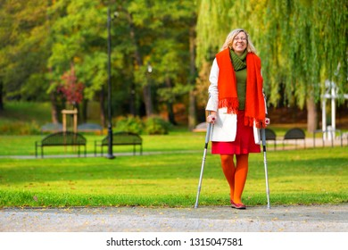 happy woman in colorful clothes standing on crutches in the autumnal park