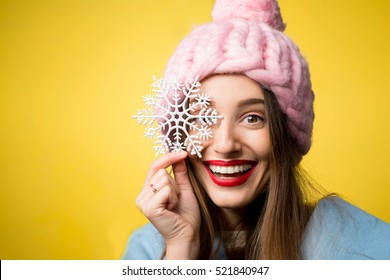 Happy woman in colorful winter clothes holding a beautiful snowflake standing on the yellow background. Happy winter concept