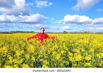 Happy woman in a colza field.