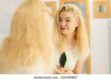 Happy woman combing her hair with brush. Young smiling female with natural blond straight long hairs in bathroom after morning shower.