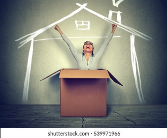 Happy woman coming out of box into a new house. Real estate concept