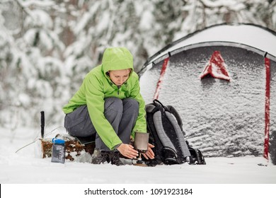 Happy woman cooking near winter tent camp in the snow forest. Bushcraft, survival and people concept