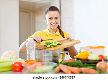 happy woman cooking  vegetables at  kitchen