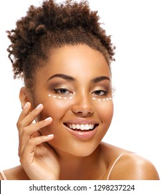 Happy woman with cream around the eyes. Photo of smiling african american woman with healthy skin on white background. Skin care and beauty concept