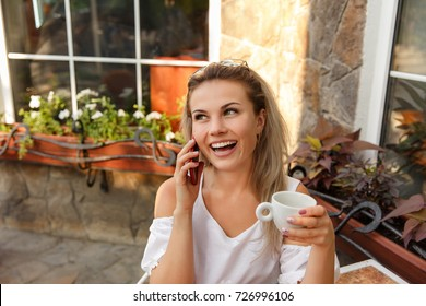 Happy woman with cup of coffee and red smart phone smiling in cafe. Young worker, freelancer or bloger with smile. Business woman calling on phone after work
