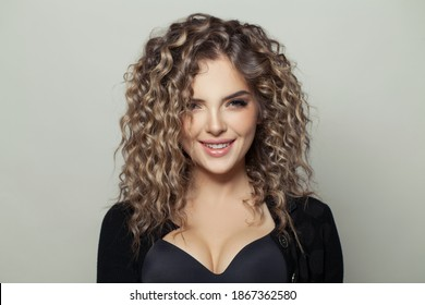 Happy woman with curly hair smiling on white background