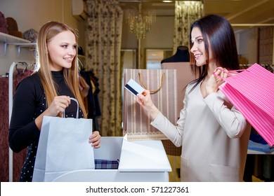 Happy woman customer paying with credit card in fashion shop
