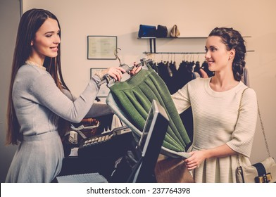 Happy woman customer paying in fashion showroom