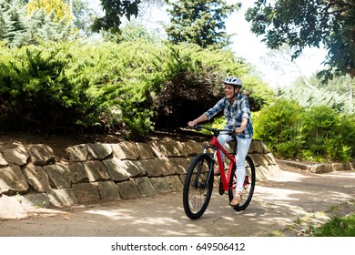 Happy woman cycling in park on a sunny day
