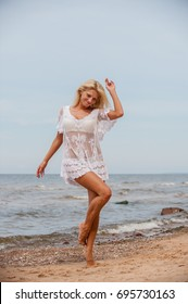 Happy woman dance by the sea in the summer