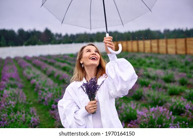 happy woman dancing under rain, holding umbrella and bouquet and smiling in overcast. shallow depth of field photo