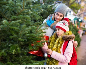 Happy woman with daughter buying Christmas tree in market. Focus on woman