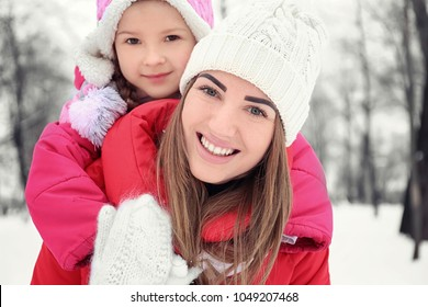Happy woman with daughter in snowy park on winter vacation