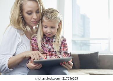 Happy woman with daughter using digital tablet in living room