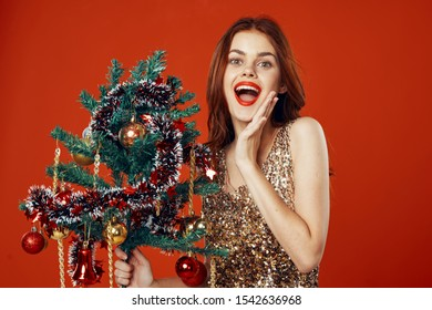 Happy woman with a decorated Christmas tree in her hand on a red background wide open her mouth fun New Year