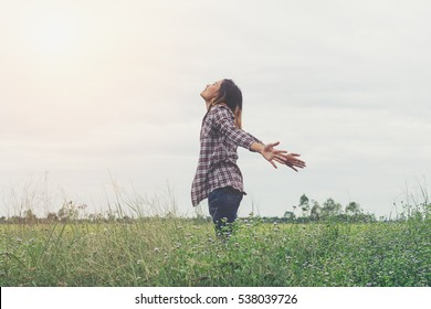 Happy woman deep breath fresh air in nature breathing clean air. Female enjoying nature. Showing to asian girl feeling happiness in freedom life with arms raised up. Happy freedom life concept.