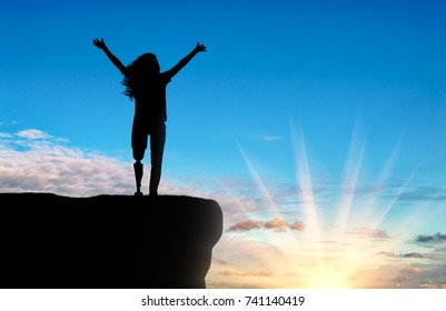 Happy woman disabled with a prosthetic leg stands at the top with outstretched hands up. The concept of happy people with disabilities with prosthetic leg