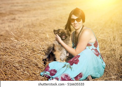 Happy woman with dog in summer sunset