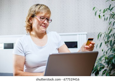 Happy woman doing her shopping online using a credit card