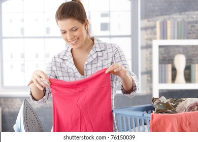 Happy woman doing laundry at home, holding clothes, smiling.?
