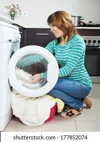 happy  woman doing laundry with washing machine at home kitchen