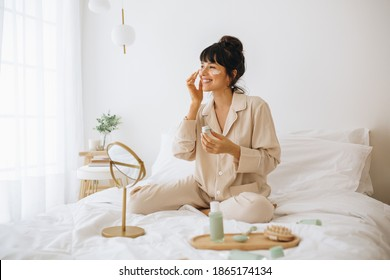 Happy woman doing routine skin care at home with beauty products. Woman sitting on bed at home and applying face cream. - Shutterstock ID 1865174134