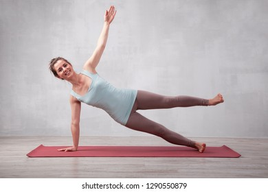 Happy woman doing sporty exercise in living room or in yoga class