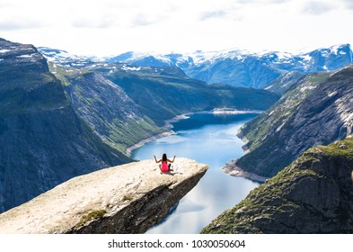 Happy woman doing yoga in cliff during trip Norway. Trolltunga hiking route