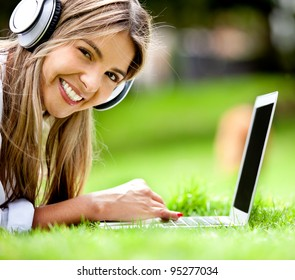 Happy woman downloading music outdoors with laptop and headphones