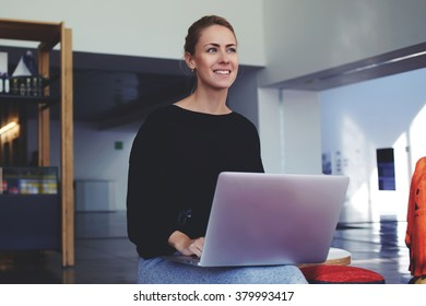 Happy woman dreaming about something while waiting until downloads the file on laptop computer, smiling female listening to the story colleague while sitting with open net-book in modern office cafe